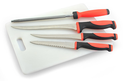 Red and black kitchen knives, with handle grips made from TPE, resting on a cutting board